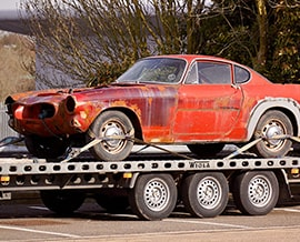 Personal-Injury-red-coupe-on-flatbed-trailer